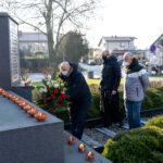 Wójt gminy Teresin Marek Olechowski, wiceprzewodniczący rady Lech Kaźmierczak i proboszcz Mariusz Książek składają kwiaty przy Pomniku 20 Rozstrzelanych